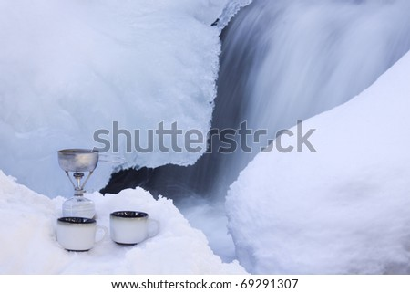 A snowshoeing trip is rimmed with romance as a couple can enjoy hot cocoa for two beside an icy waterfall. - stock photo