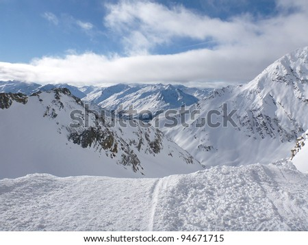 A snowy mountain scene in a ski resort, showing what looks like the edge of the world.  Taken on a sunny day. - stock photo