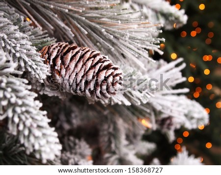 A snowy pinecone decorated Christmas tree, with bokeh lights in the background. - stock photo