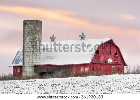 A snowy red barn with silo and basketball hoop is seen with a sunset sky of soft colors. - stock photo