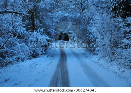 A snowy road in winter in Surrey, England - stock photo