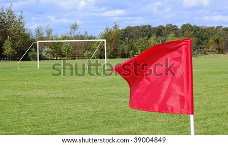 A soccer field with a goal and a red flag - stock photo