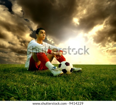 a soccer player sitting on the field - stock photo