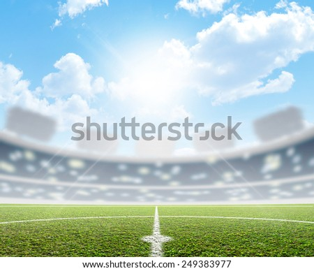 A soccer stadium with a marked green grass pitch in the daytime under a blue sky - stock photo