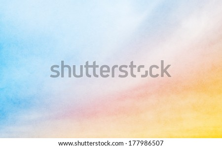 A soft cloud background with a pastel colored orange to blue gradient.  Image displays a pleasing paper grain and texture at 100 percent. - stock photo