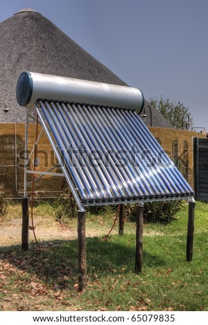 A solar thermal installation, providing hot water to a rural, thatched building behind - stock photo