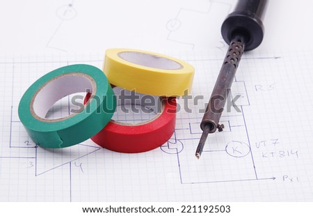 A soldering iron and adhesive plastic tape on the background of the electric scheme - stock photo