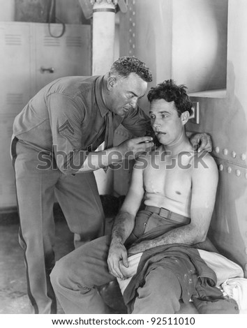 A soldier helps his comrade and lets him smoke his pipe - stock photo