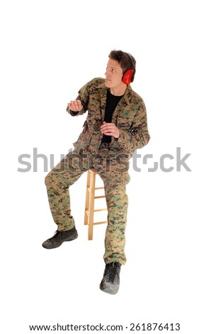 A soldier in camouflage uniform sitting on a chair in a scary positionwith ear protection, isolated for white background. - stock photo