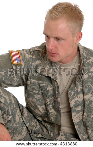 A soldier in combat fatigues sitting on the grou8nd - stock photo