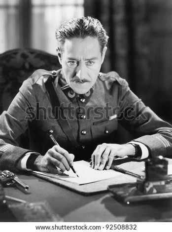 A soldier writing a letter with a gun next to him - stock photo