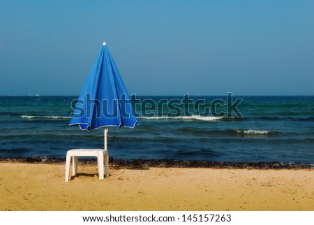A solitary blue beach umbrella and a white plastic table on a sandy beach close to the water's edge. - stock photo