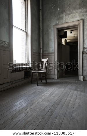A solitary chair facing the window in a abandoned room with old wood floors and high ceiling. - stock photo