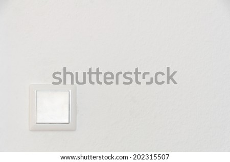 a solitary light switch on a white wall - stock photo