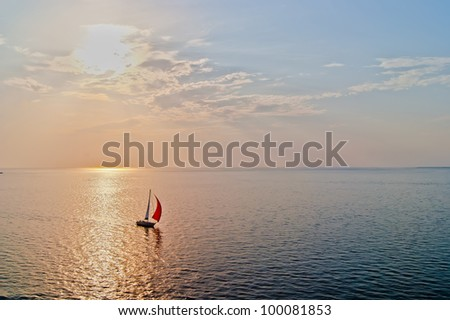 A solitary sailboat in the open sea at the sunset, bird's-eye view - stock photo