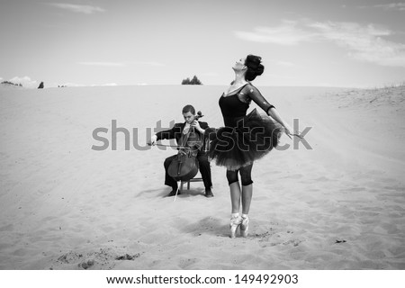 A solo cellist plays for an elegant ballerina dancing in the barren desert. - stock photo