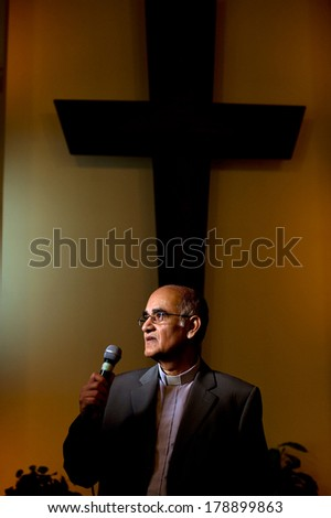 A south asian pastor with a large cross behind him, speaking to his congregation with a microphone - stock photo