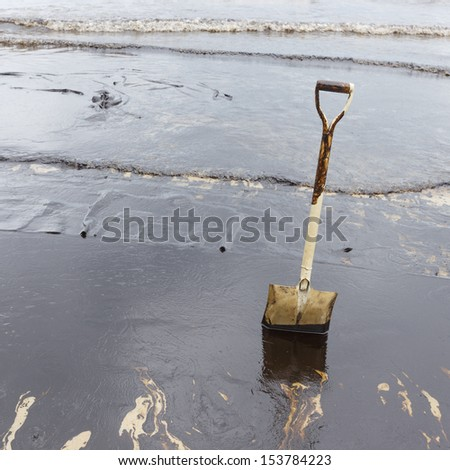 A Spade on dirty beach as tool to scoop crude oil on clean-up operation from crude oil spilled into Ao Prao Beach on July 31, 2013 in Rayong province, Thailand. - stock photo
