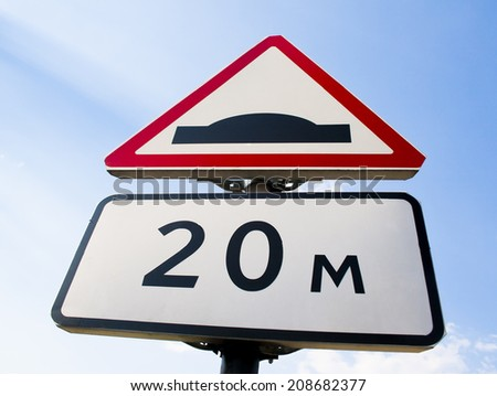 a speed bump sign in a road over the sky - stock photo