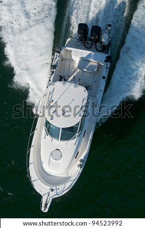 A speedboat moving through calm water in the Pacific Ocean. - stock photo