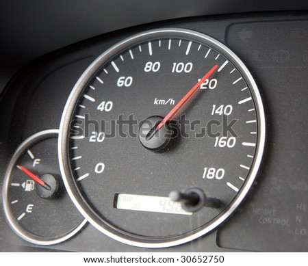 A speedometer races past hundred. - stock photo