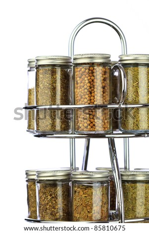 a spice rack with white isolate background, filled with fresh organic spices and herbs - stock photo