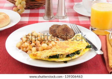 A spinach and feta cheese omelet with sausage and hash browns - stock photo