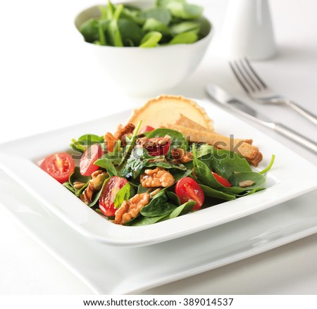 A spinach salad with cherry tomatoes, walnuts, goat cheese and balsamic vinegar. - stock photo