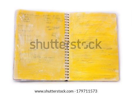 A spiral notebook with layers of acrylic paint over obscured text lines, against a white background - stock photo