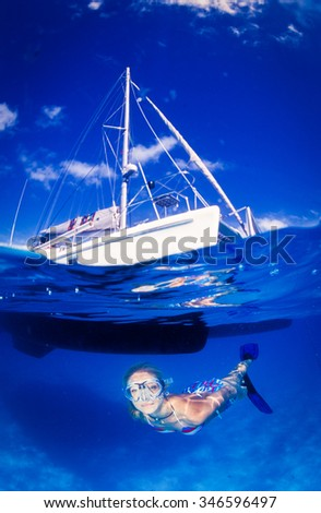 A split level photograph of a blonde woman swimming in very clear, blue water next to a white boat - stock photo
