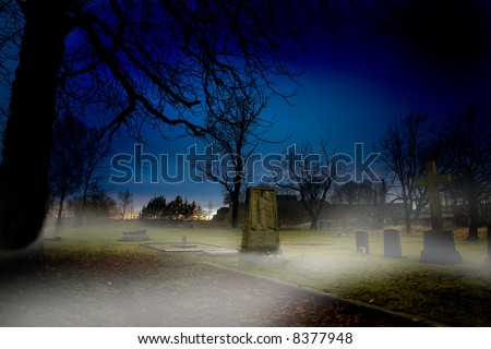 A spooky graveyard at sundown with mist - stock photo
