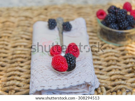 A spoon of fresh blackberries over antique lace napkin and  wicker background. Space for your text. - stock photo