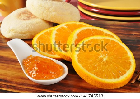 A spoonful of orange marmalade and fresh English muffins - stock photo