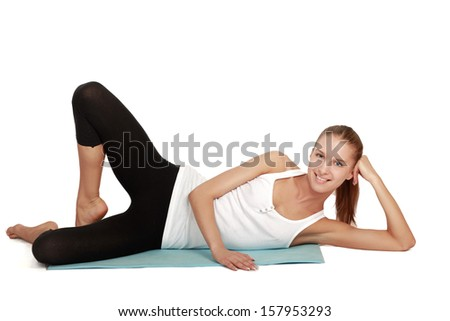 A sportive young woman lying on the floor , isolated on white background - stock photo