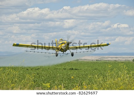 A spray plane applies chemicals to a field of potatoes. - stock photo