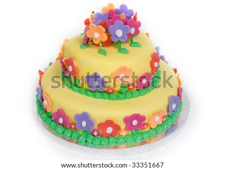 A spring-fresh fondant-covered cake, decorated with daisies both large and small, sits isolated on white. - stock photo