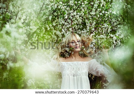 A spring image of beautiful young woman at apple tree flowers  blossoms background. - stock photo