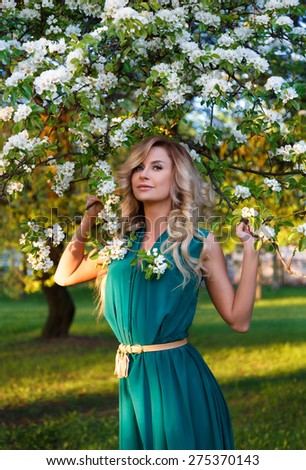 A spring image of beautiful young woman at apple tree flowers blossoms background.beautiful girl in the apple blossoms. - stock photo