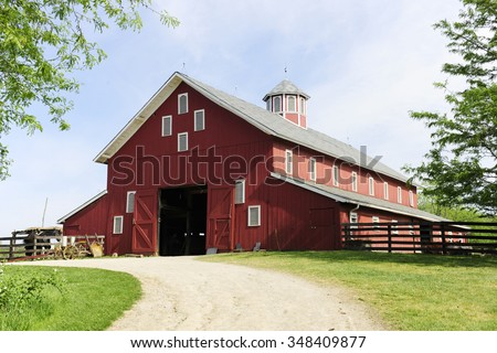 A springtime image taken on the trail leading to the open doors of a big red barn on a sunny day. - stock photo