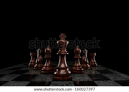 A squad of 7 chess pieces leaded by the king. - stock photo