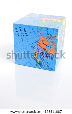 A square block that has a map of the world on it. - stock photo