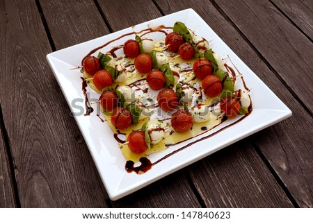 A square white plate with sticks of cherry tomatoes, Italian Mozarella cheese balls and fresh basil leaves topped with olive oil and balsamic vinegar served as starter on an old wooden table outside. - stock photo
