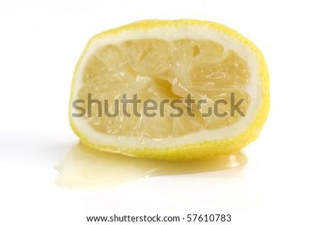 a Squeezed lemon lying in it's on juice - stock photo