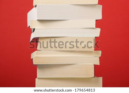 A stack of assorted paperback books against a deep red background - stock photo