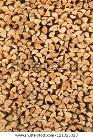 A stack of birch firewood - a natural vertical background - stock photo