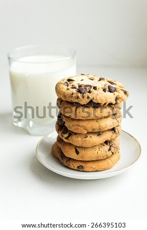 A stack of Biscuit cookies with chocolate chips and a glass of milk - stock photo