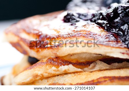 a stack of blueberry pancakes with butter, syrup and fresh berries - stock photo