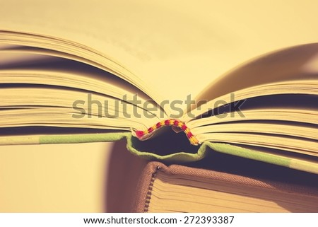 A Stack of Books with Opened Book on Top - stock photo