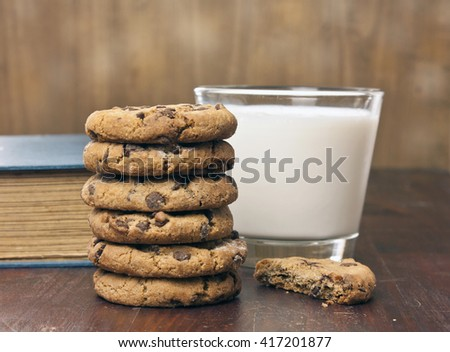 A stack of chocolate chips cookies and a half of one, with a glass of milk and an old book in the background - stock photo