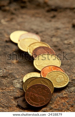 A stack of coins over the stone background. Shallow DOF - stock photo
